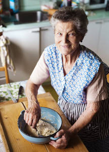 Picture of elderly woman in a blue dress mixing ingredients together in a bowl.
