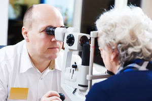 Picture of optometrist giving an eye exam to an elderly lady.
